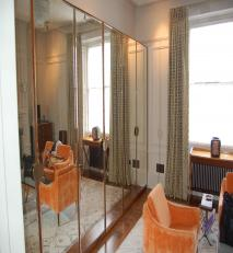 Mirrored wardrobe doors with the end door concealing the entrance to an en-suite bathroom.