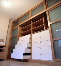 Ample drawer space in this fitted wardrobe with frosted glass sliding doors.