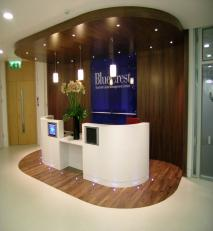 Solid surface reception desk with walnut bulkhead and curved storage wall.