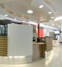 Oval reception desk in european oak featuring curved, painted glass panels.