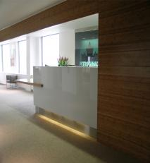 Split level reception desk in solid oak and white painted glass.