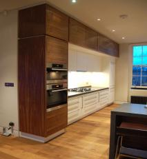 Walnut veneer and white lacquered kitchen with Zodiak® work surfaces.