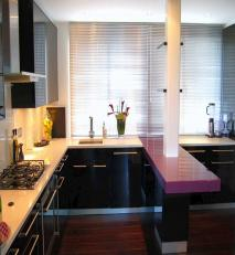 Fitted kitchen finished in black gloss lacquer with coloured glass breakfast bar.