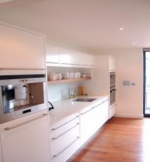 Simple kitchen in white with stainless steel fittings.