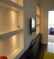 AV unit with lit alcove shelving.