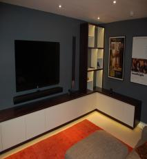 AV unit with storage in dark stained oak and colour lacquer with dimmable LED lighting.