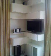 Bespoke corner storage unit, using what was a dead space between two windows. In a white spray lacquered finish.